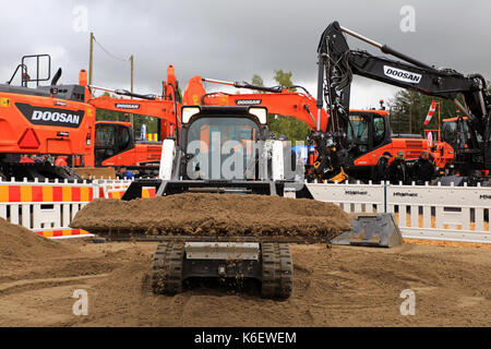 HYVINKAA, FINLAND - SEPTEMBER 8, 2017: Operator sifts sand with land leveler mounted on Bobcat T450 Compact Track - Stock Photo