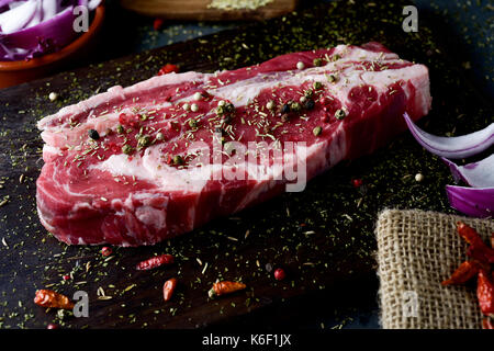 closeup of a raw strip steak seasoned with different spices, such pepper corns of different colors or oregano, on - Stock Photo