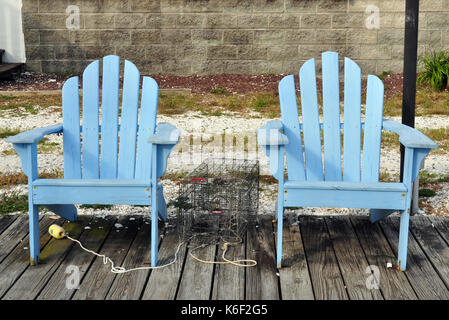 Two Blue Adirondack Chairs On A Grassy Beach With Rock
