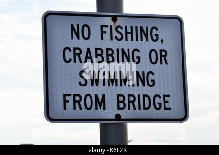 A Sign that reads 'No Fishing Crabbing or Swimming from Bridge'.  Black printing on a white background. - Stock Photo