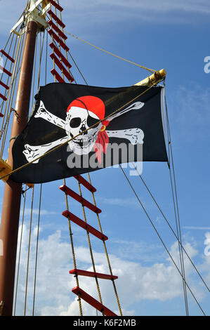 Black, White, and Red Pirate Flag flying on a ship against a blue sky. - Stock Photo