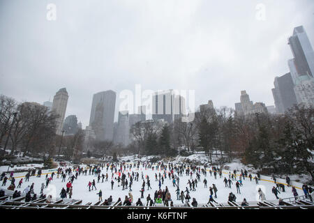 Crowd of people ice skating on Wollman Rink in Central Park in New York City during the winter, USA - Stock Photo