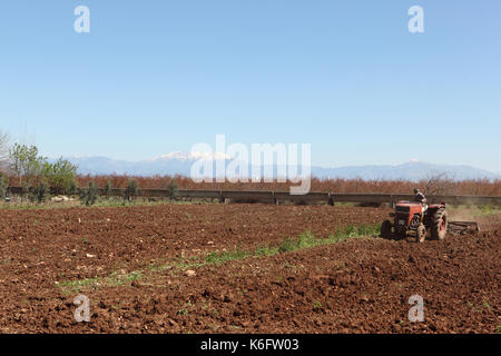 old tractor ploughing field with mountain covered in snow backgrounds - Stock Photo