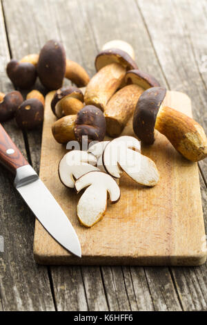 Sliced boletus mushrooms on cutting board and knife. Tasty food mushrooms. - Stock Photo