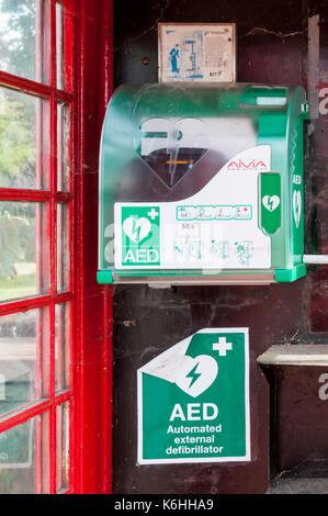 Public defibrillator in old telephone kiosk - Stock Photo