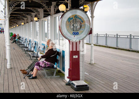 An old fashioned, stand on, coin operated, weighing scales at the end on an English seaside pier - Stock Photo