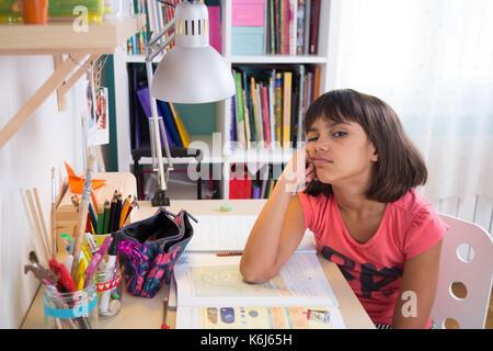Bored school girl doing homework at home. Looking at camera - Stock Photo