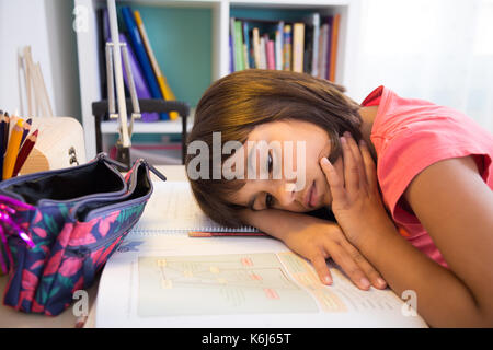 Exhausted school girl doing homework at home - Stock Photo