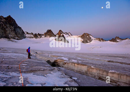 Alpinist at a crevasse on the glacier Plateau du Trient at full moon, Valais, Switzerland - Stock Photo