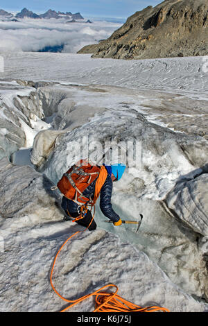 Alpinist examing a crevasse on the Plateau du Trient, Valais, Switzerland - Stock Photo