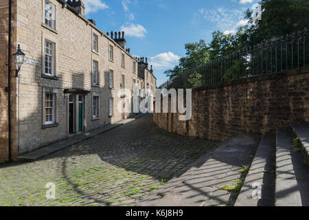 Sunlight and shadows on the steps, Georgian buildings and deserted cobbled street in the historic city of Lancaster, - Stock Photo