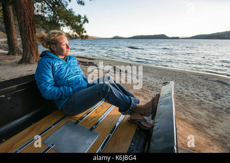 Woman sitting in renovated truck watching sunset, Payette Lake, McCall, Idaho, USA - Stock Photo