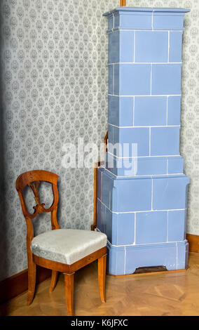 Historic tiled stove in the corner of the hall with a decorative upholstered chair. - Stock Photo