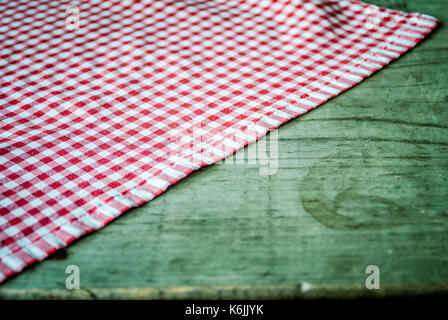 Old, wooden, green table with a red checkered tablecloth on the table - Stock Photo