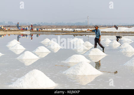 NHA TRANG, VIETNAM - 4/12/2016: Workers and piles of salt at the Hon Khoi salt fields in Nha Trang, Vietnam. - Stock Photo