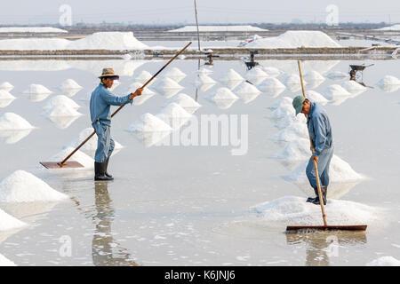 NHA TRANG, VIETNAM - 4/12/2016: Two men organize salt into piles at the Hon Khoi salt fields in Nha Trang, Vietnam. - Stock Photo