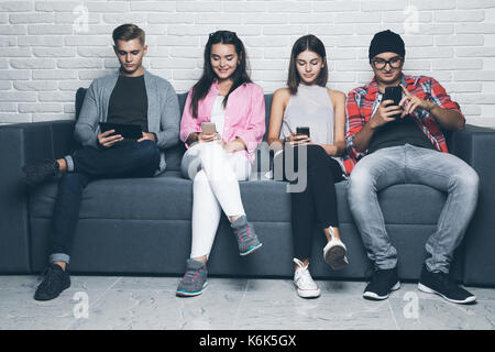 Young people looking down at cellular phone. Sitting on the couch and ignoring each others with on the smart phones. - Stock Photo