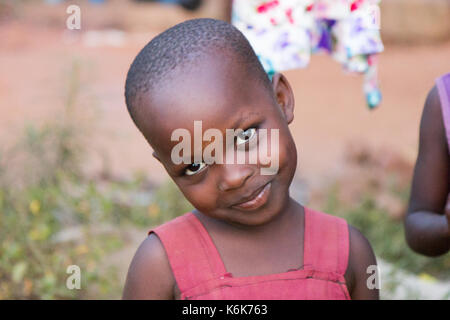 A cute little black preteen age girl tilting her head smiling. She is dressed in a red dress. - Stock Photo