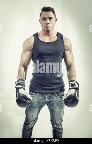 Muscular man in boxing gloves - Stock Photo