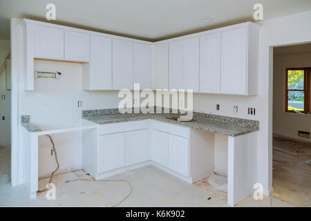Installing new induction hob in modern kitchen kitchen Installation of kitchen cabinet. - Stock Photo