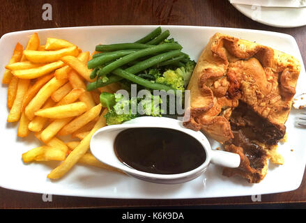 British lunch - Steak pie with chips, broccoli and gravy - Stock Photo