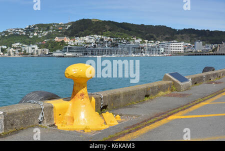 Yellow Bollard on the Wellington Harbour Waterfront and Mount Victoria in the background, New Zealand. - Stock Photo