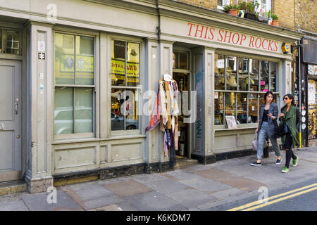 Two woman walking past This Shop Rocks secondhand clothing, furniture and book shop in Brick Lane, London - Stock Photo