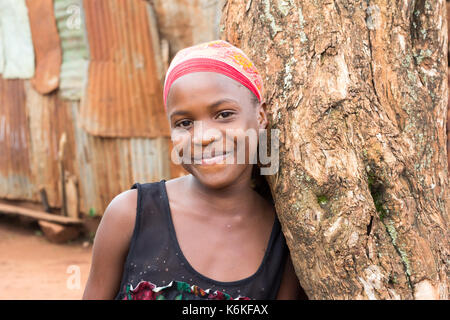 A beautiful black teenage girl smiling and leaning against a tree. She is wearing a red headscarf. - Stock Photo