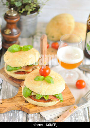 a hamburger with a meatball and cheese, is decorated with greens and tomatoes. beer in a glass and a bottle. Tasty - Stock Photo