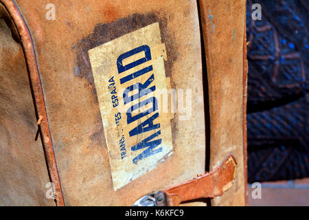 Old brown leather suitcase with worn label reading Madrid, found in a flea market - Stock Photo