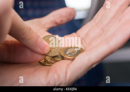 Picking out an old pound coin from a handful of new pound coins - Stock Photo