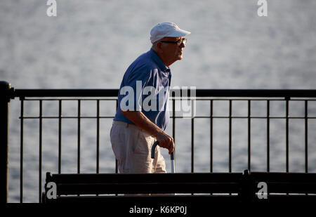 Old man with a cane walking along the waterfront in Piers Park, East Boston, Massachusetts - Stock Photo