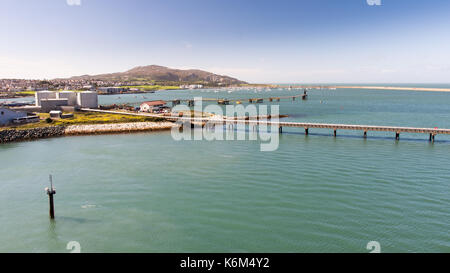Piers and fuel tanks at Holyhead Port in North Wales, with Holyhead town and Holyhead Mountain behind. - Stock Photo