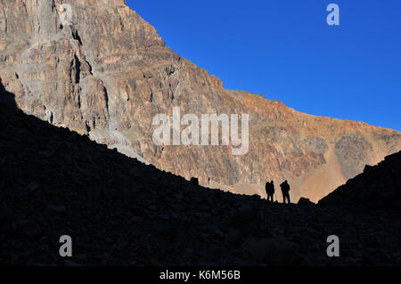 Morocco, North Africa, High Atlas Mountains. Two friends trekking on the rocky mountain path against the rocks and - Stock Photo