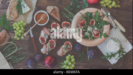 Easy diet salad with arugula, figs and blue cheese on a brown wooden surface. Sandwiches with ricotta, fresh figs, - Stock Photo