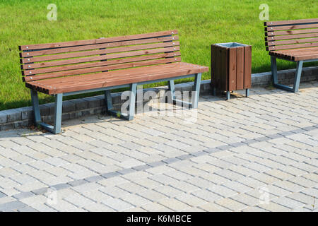 Two stylish benches and a trash can in a summer park along a paved path against a green lawn. Small architectural - Stock Photo