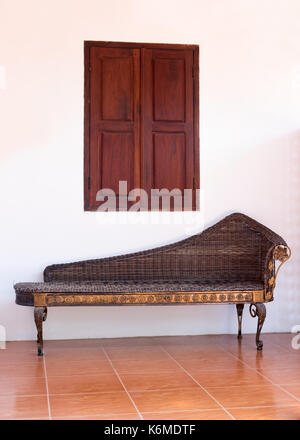 empty rattan sofa under a window with wooden shutters, Laos - Stock Photo