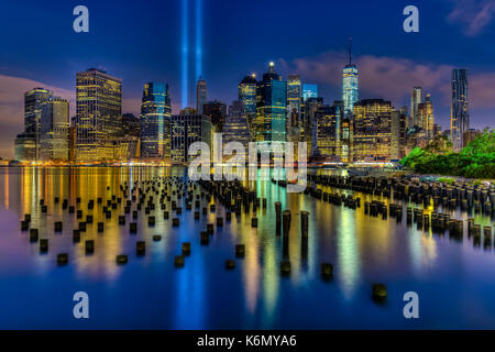 September 11 NYC Tribute - Two beams of light shine high into the blue sky at the lower Manhattan skyline during - Stock Photo
