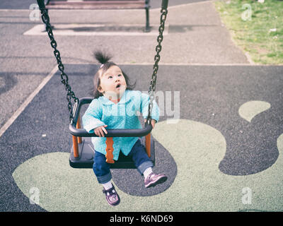 baby girl playing swing in the  playground - Stock Photo