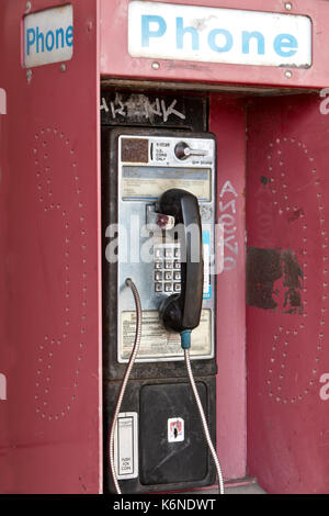 Abandoned 'Antique' coin operated public telephone with coin release slot, graffiti, old shopping center, California, - Stock Photo