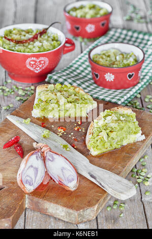 Cream of green split peas with sauce of olive oil and fried onions, in little bowls and spread on bread slices. - Stock Photo