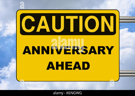 Anniversary ahead, caution yellow road sign - Stock Photo