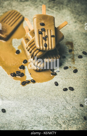 Flatlay of melting coffee latte popsicles with beans, copy space - Stock Photo