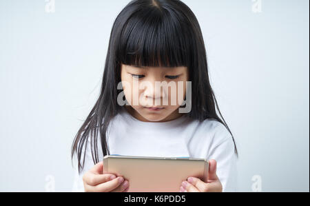 Little asian chinese girl using smartphone  . - Stock Photo