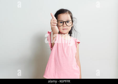 Little girl dressed in pink is showing thumb up gesture , isolated over white background . - Stock Photo
