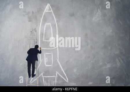 Businessman climb stair drawing rocket sketch on wall , Success, leader and winner concept . - Stock Photo