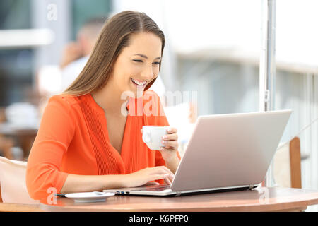 Single happy woman browsing a laptop on line seated in a bar - Stock Photo