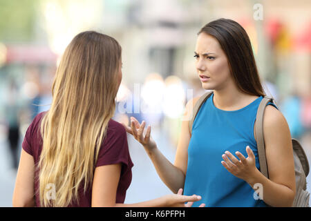 Two angry women friends talking seriously on the street