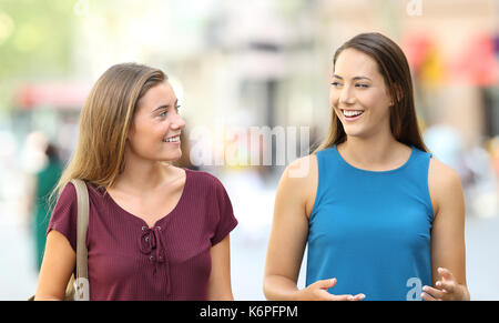 Two happy friends walking towards camera and talking on the street - Stock Photo