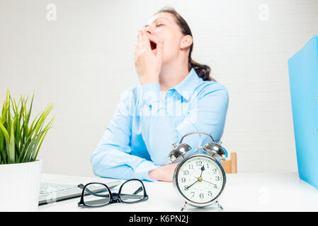 Closeup alarm clock and yawning tired businesswoman at the office - Stock Photo